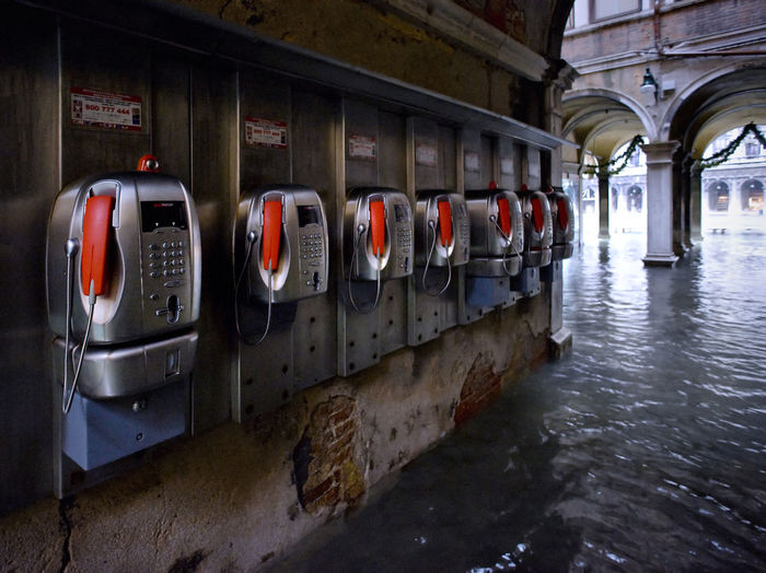 Pay phones on wall by water filled walkway during flood at st marks square