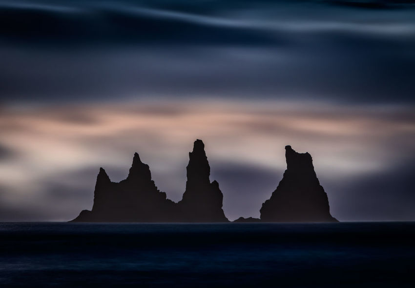 Basalt stacks as seen from Reynisfjara, a world-famous black-sand beach found on the South Coast of Iceland, just beside the small fishing village of Vík í Mýrdal. Iceland Basalt Columns Beauty In Nature Cloud - Sky Dusk Idyllic Land Nature No People Outdoors Reynisfjara Rock Rock - Object Rock Formation Scenics - Nature Sea Sea Stacks Silhouette Sky Solid Stack Rock Sunset Tranquil Scene Tranquility Water