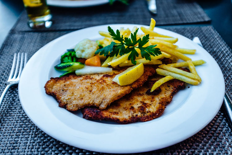 Schnitzel with french fries served in plate on table