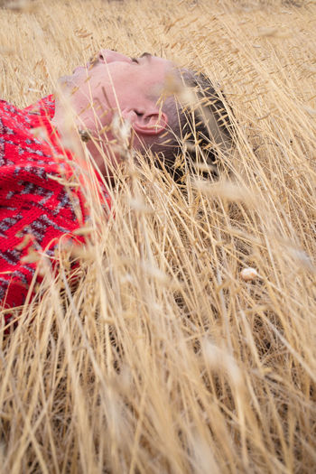 Midsection of woman with hay bales in field