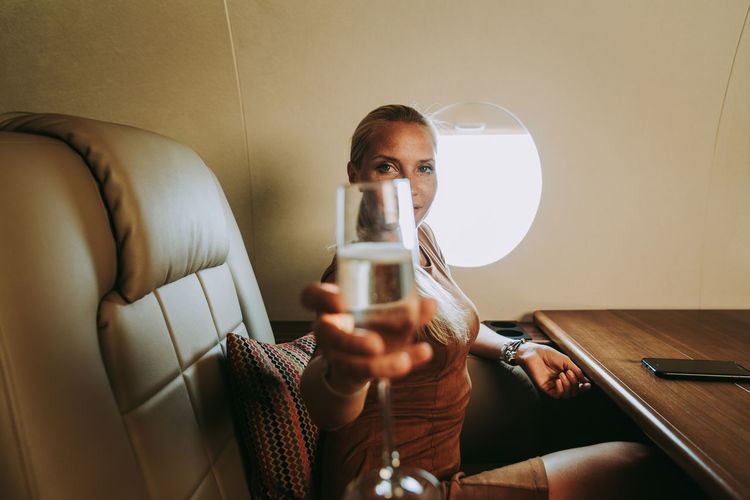 Portrait of businesswoman holding wineglass in airplane