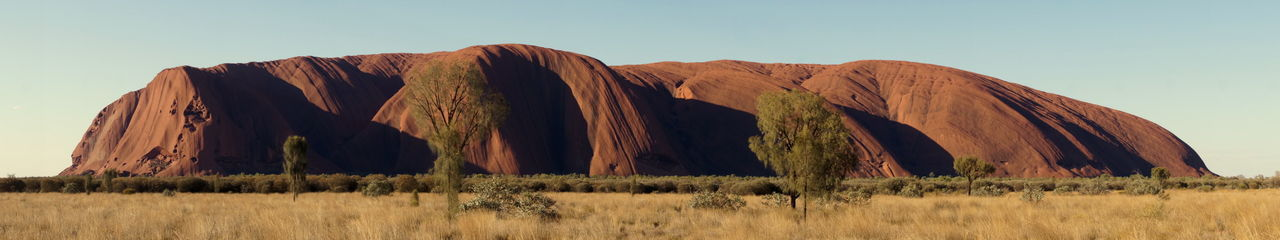 Ayers Rock National Park Ayers Rock Red Uluru Beauty In Nature Clear Sky Day Field Grass Landscape Mountain Nature No People Outdoors Panoramic Physical Geography Plant Reddish Reddish Brown Rural Scene Sand Dune Scenics Sky Tranquil Scene Travel Destinations