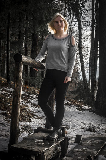 Young woman looking away while standing in forest during winter