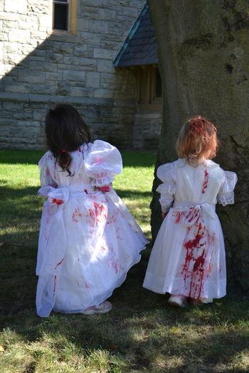 Rear view of girls wearing halloween costume standing on field