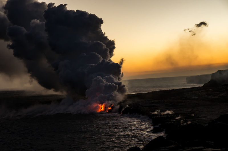 High Angle View Of Lava Flowing Into Sea At Big Island During Sunset
