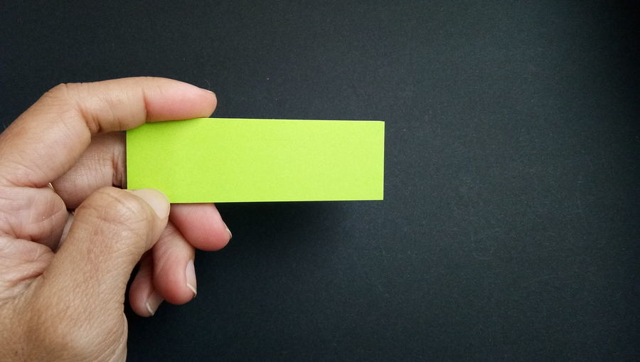 Cropped Hand Of Person Holding Blank Green Adhesive Note On Table