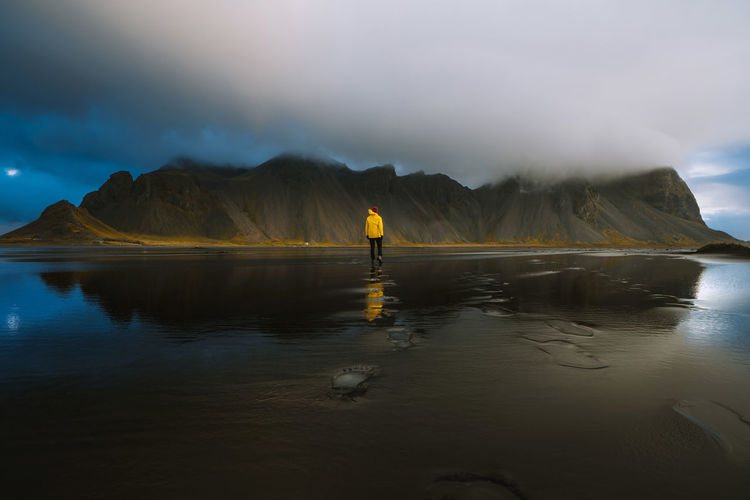 Walking along the black sands of Iceland Check out my print store at http://simonmigaj.com/shop/ and visit my Instagram at http://www.instagram.com/simonmigaj to find out more about me and my work Iceland Stokksnes Travel Adventure Beauty In Nature Cloud - Sky Landscape Lifestyles Mountain Mountain Range Non-urban Scene One Person Outdoors Reflection Scenics - Nature Sky Tranquil Scene Tranquility Water