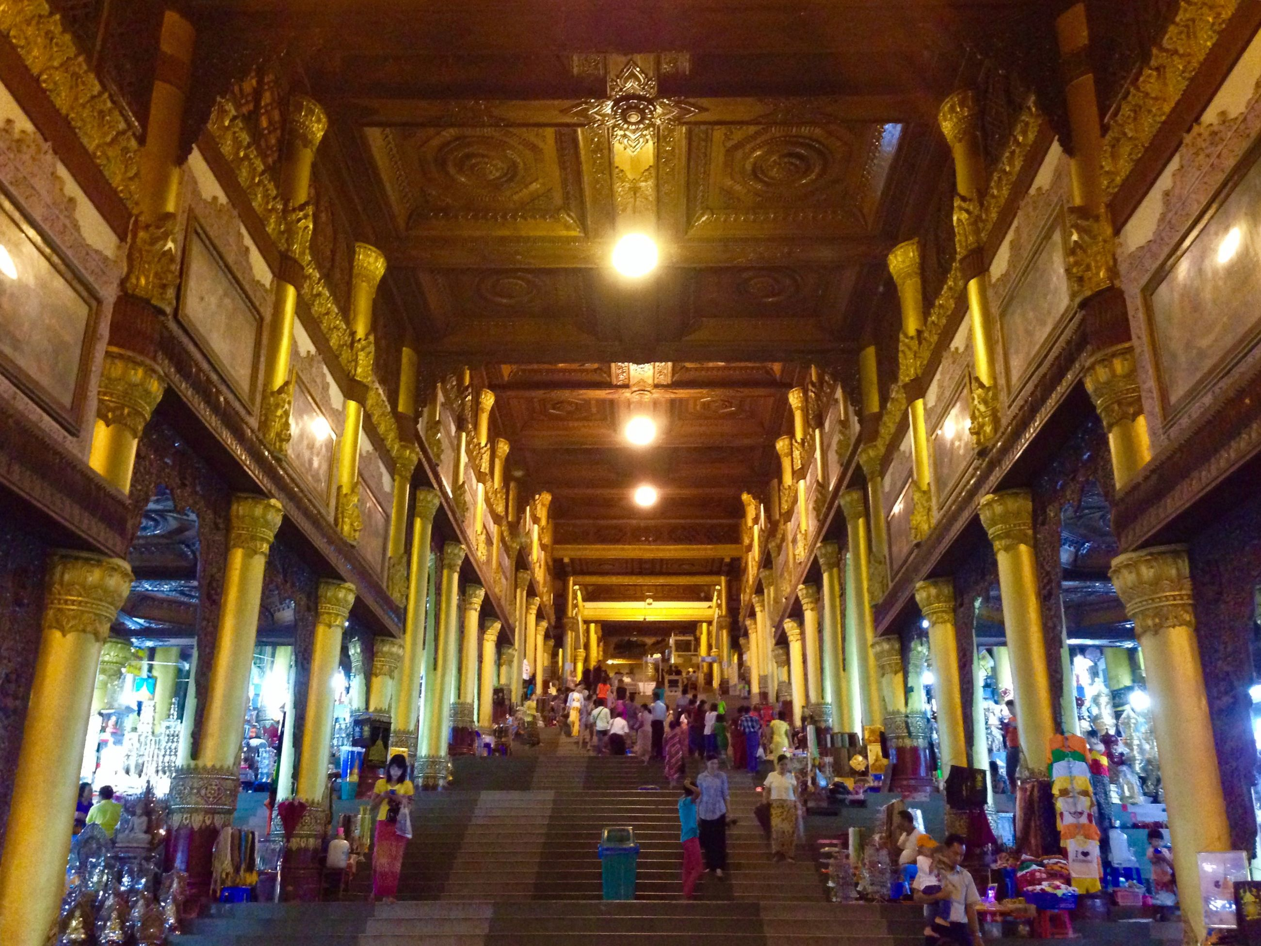 large group of people, indoors, person, illuminated, ceiling, architecture, men, built structure, lifestyles, lighting equipment, leisure activity, architectural column, the way forward, walking, mixed age range, group of people, shopping, travel, in a row