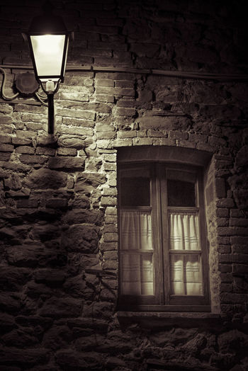 Low angle view of illuminated lamp on wall of old building