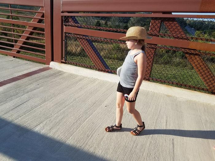 Cute girl walking on footbridge