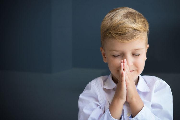 Close-Up Of Smiling Cute Boy Praying
