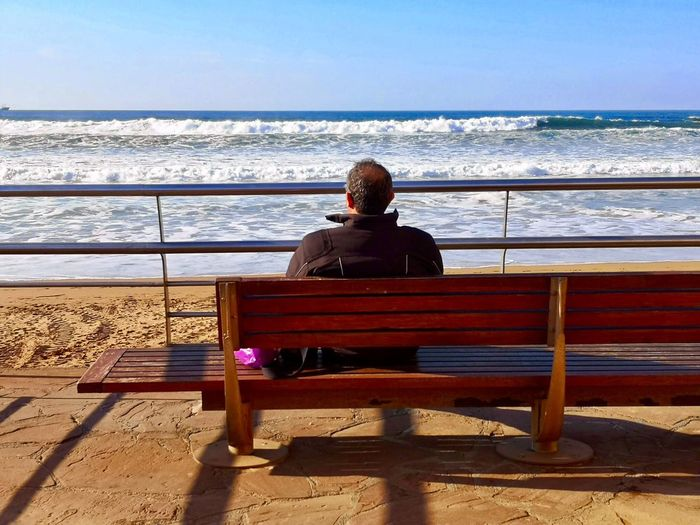 Sea Sitting One Person Water Rear View Real People Lifestyles Nature Sunlight Seat Beach Day Horizon Over Water Outdoors