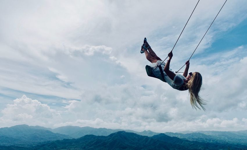 Low angle view of woman on swing against sky