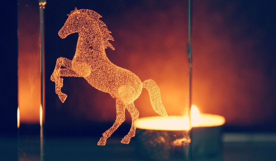 Close-up of horse carved on glass against lit tea light