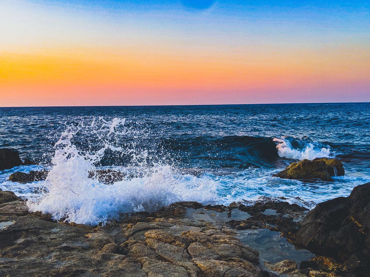 SCENIC VIEW OF SEA WAVES SPLASHING ON ROCKS AT SUNSET