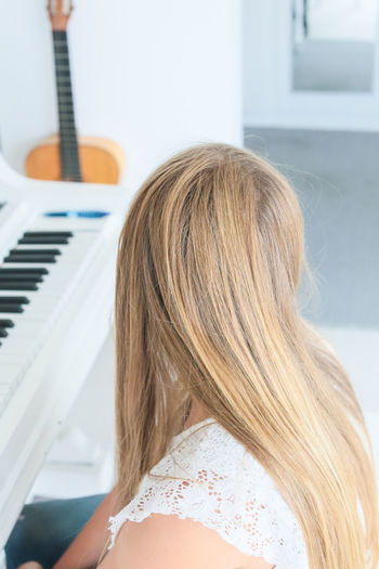 High angle view of blond woman sitting by grand piano at home
