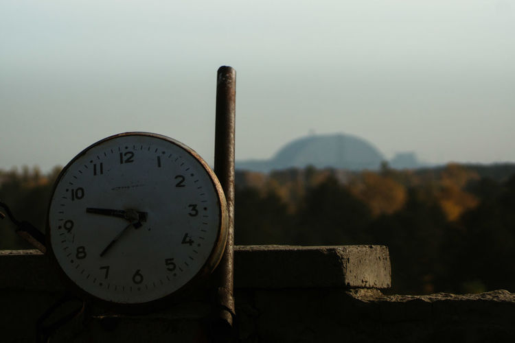 Close-up of clock on wood against sky