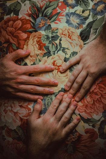 Cropped hands of people over flower design sheet