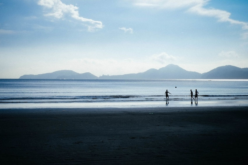 Silhouettes of Kids playing Football at the beach with mountains and calm mood Adult Adults Only Beach Beauty In Nature Cloud - Sky Day Full Length Horizon Over Water Kids Being Kids Kids Having Fun Kids Playing At The Beach Men Mountain Nature Only Men Outdoors People Real People Scenics Sea Sky Togetherness Two People Water Wave Live For The Story