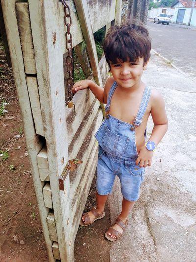 Portrait of cute boy standing by wooden gate