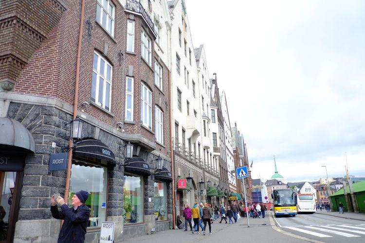 People walking on street amidst buildings in city against sky