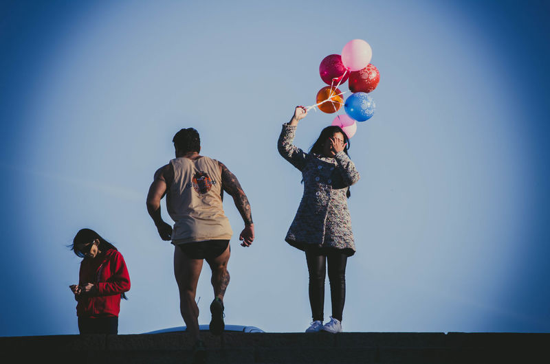 Rear view of people standing on balloons against blue sky