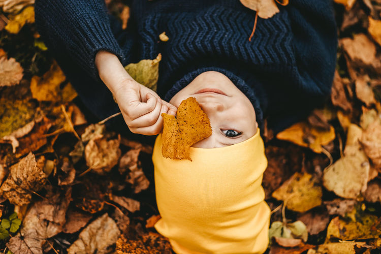 Portrait of a boy a child in a yellow hat holding an autumn leaf and lying in the fall park outdoors
