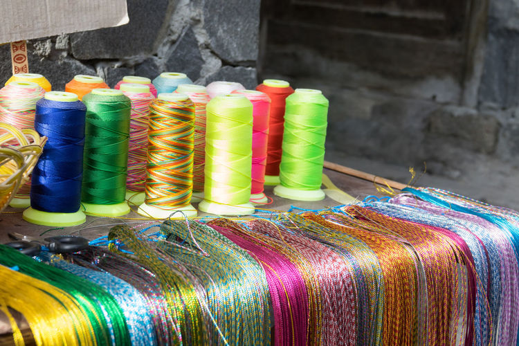 Spools of colorful silk thread on shelf Multi Colored Thread Spool No People Industry In A Row Textile Textile Industry Choice Variation Focus On Foreground Large Group Of Objects Rolled Up Indoors  Factory Manufacturing Equipment Close-up Day For Sale Silk Color