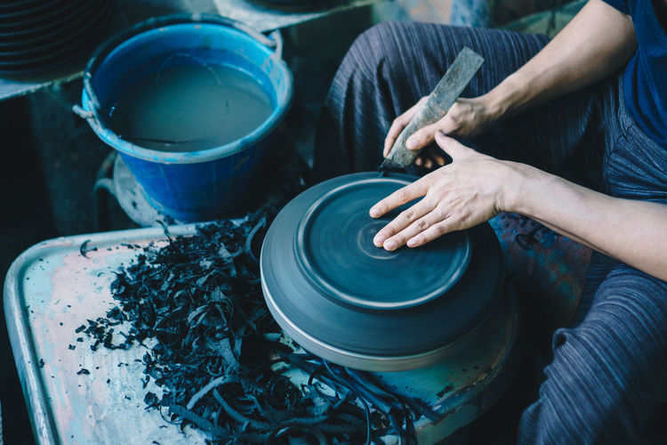 Midsection of man making pottery in workshop
