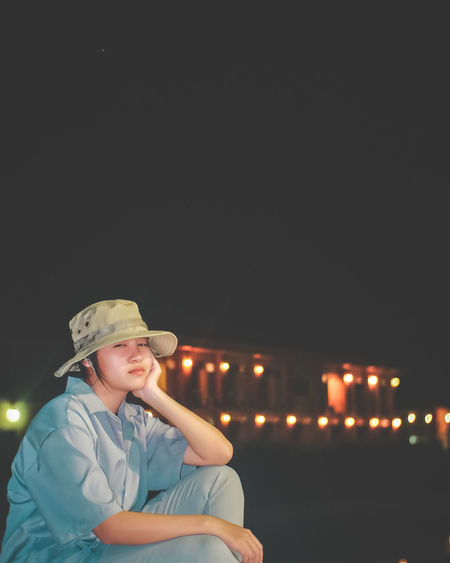 Portrait of smiling girl wearing hat sitting outdoors