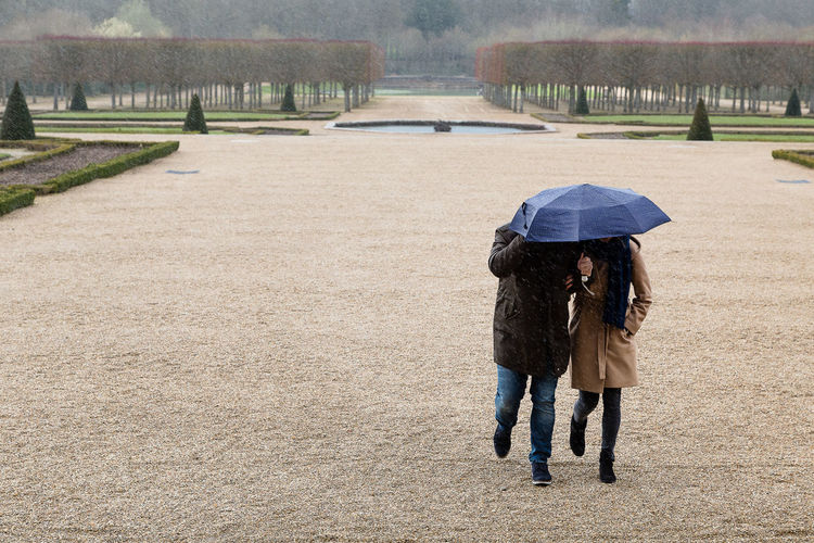 Couple Holding Umbrella While Walking In Park During Rainy Season