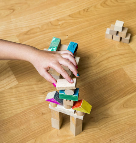 Had of a children arranging wooden toys. Children Construction Fun Funny Room Childhood Close-up Cubes Fingers Game Girl Hardwood Floor Human Body Part Human Hand Indoors  Kid Kids Room One Person Play Wooden Toys