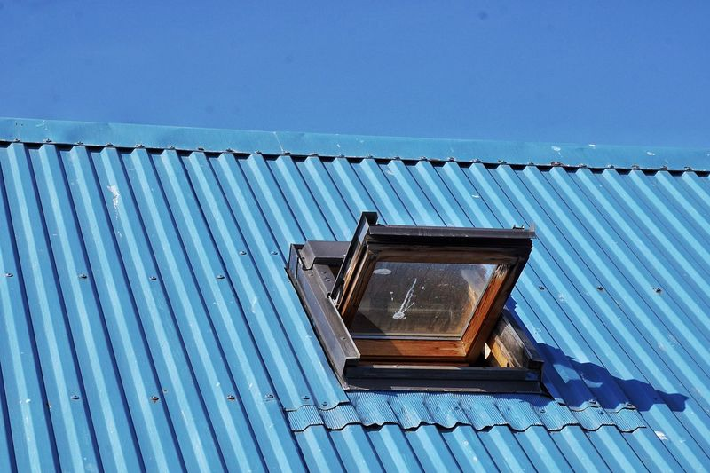 Low Angle View Of Open Window On Blue Metallic Roof Against Clear Sky