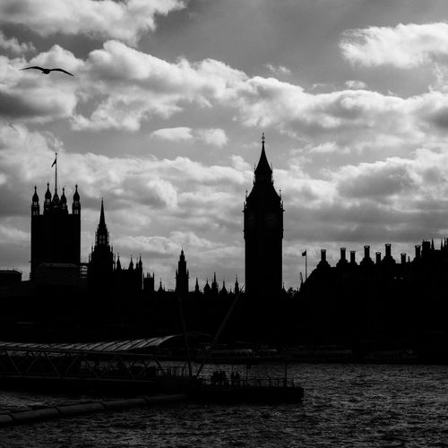 Silhouette big ben against cloudy sky