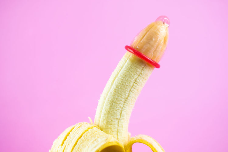 closeup condom on banana with pink background (World AIDS Day concept), soft focus. Love Condom Safety Safe Prevention Prevent Save Protection Protect Aids Care Virus Hiv Adult Relationship Rubber Contraceptive Romance Control Fruit Pink Color Banana