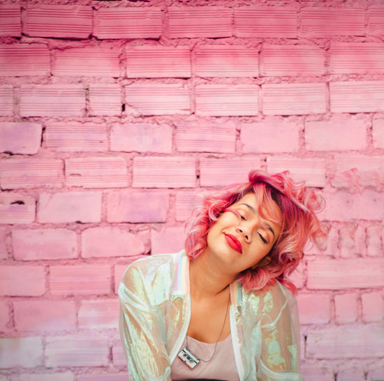 Woman with dyed hair against pink wall