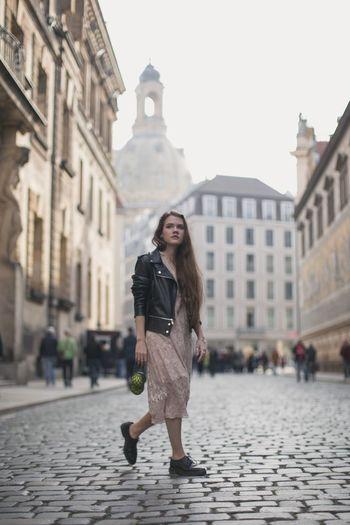 Full length of woman walking on street against buildings in city