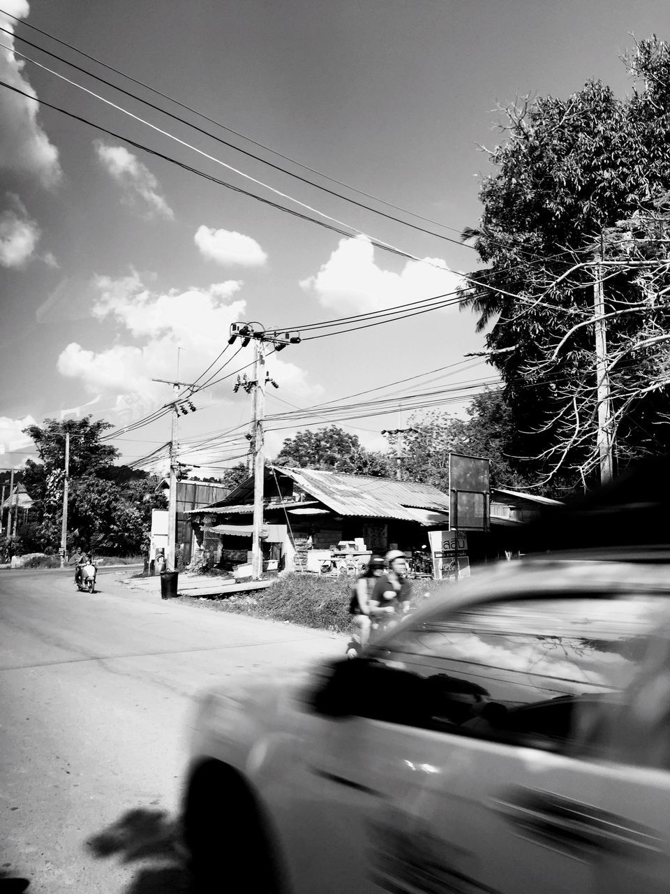 car, transportation, cable, tree, sky, mode of transport, land vehicle, road, power line, day, cloud - sky, outdoors, electricity pylon, electricity, built structure, architecture, telephone line, city, building exterior, nature, no people