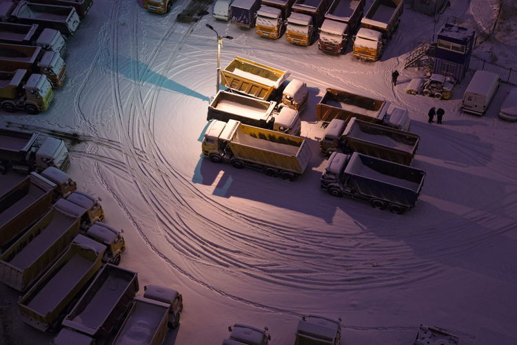 A group of trucks is seeen on a parking lot covered with snow. Logistics Transportation Twilight Winter Big Group Commercial High Angle View Kamaz Leasing Light Stand Night Outdoors Parking Snow Trucks Fresh On Market 2017
