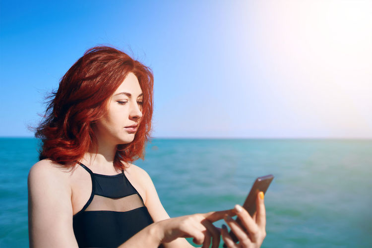Beautiful young woman using smart phone against sea