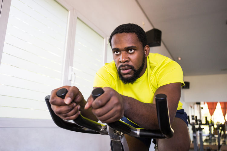 Male Athlete Cycling On Exercise Bike In Gym