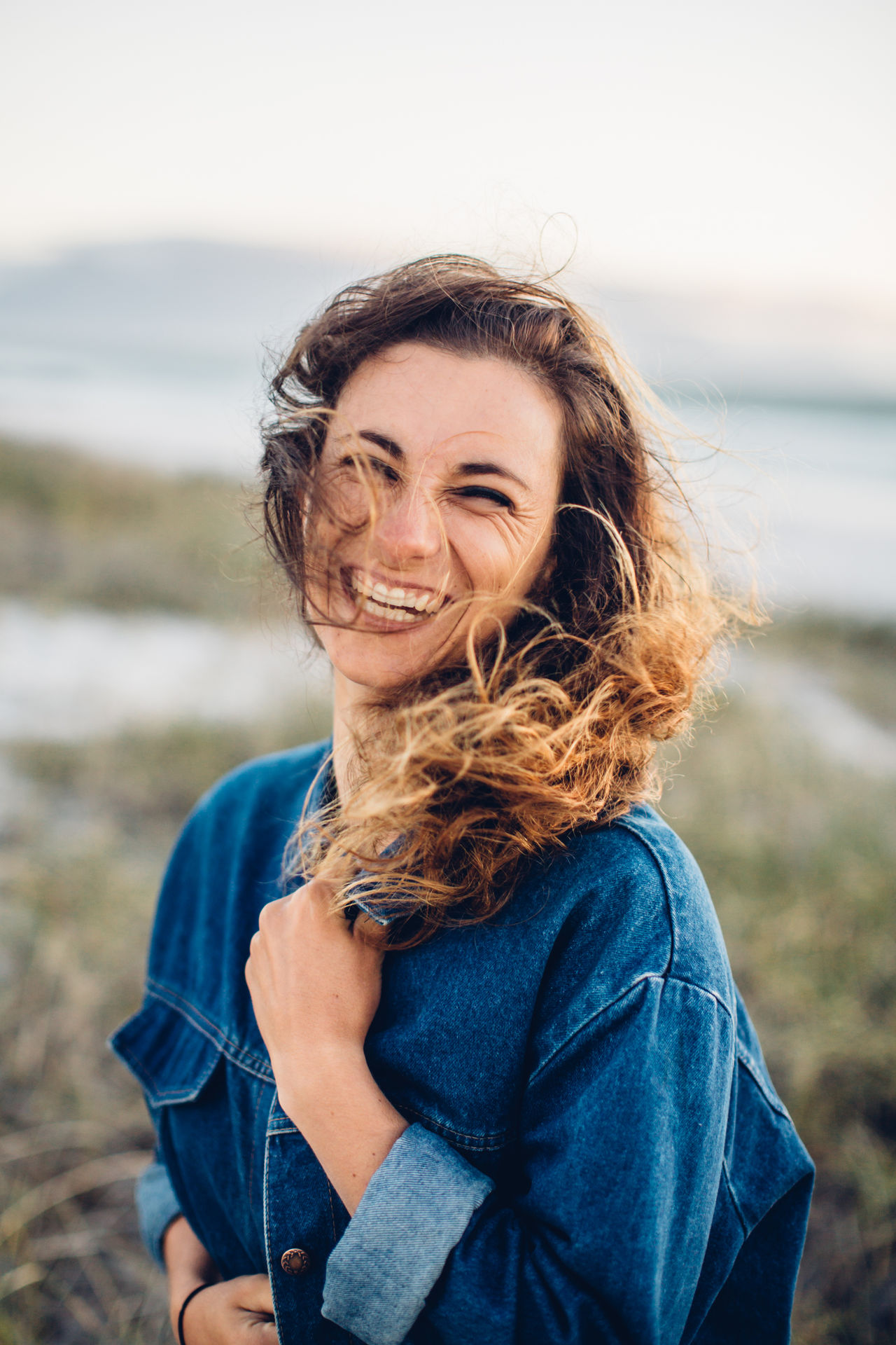 Portrait of cheerful young woman standing at beach against clear sky during sunset