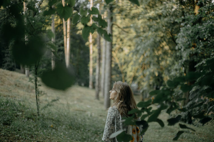 Rear view of woman standing by plants in forest