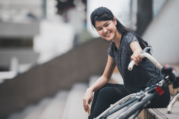 Portrait of a smiling young woman riding bicycle