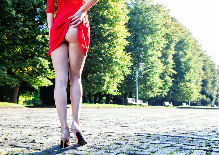 Low section of seductive woman showing buttocks while standing on footpath