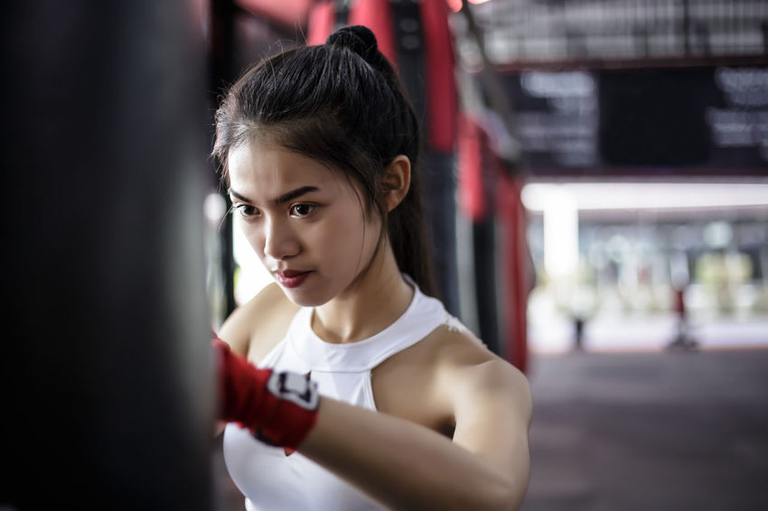 She is punching and exercising at sport woman love Boxing. ASIA Angry Asian  Boxing Cool Determination Exercising Fun Love Thai Beautiful Woman Gym Kick Boxing Lifestyles Looking Portrait Punch Sport Sport Woman Sports Standing Strength Strong Time Young Adult