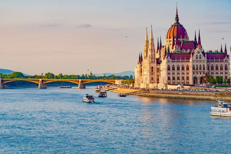 Hungarian parliament building by river against sky during sunset
