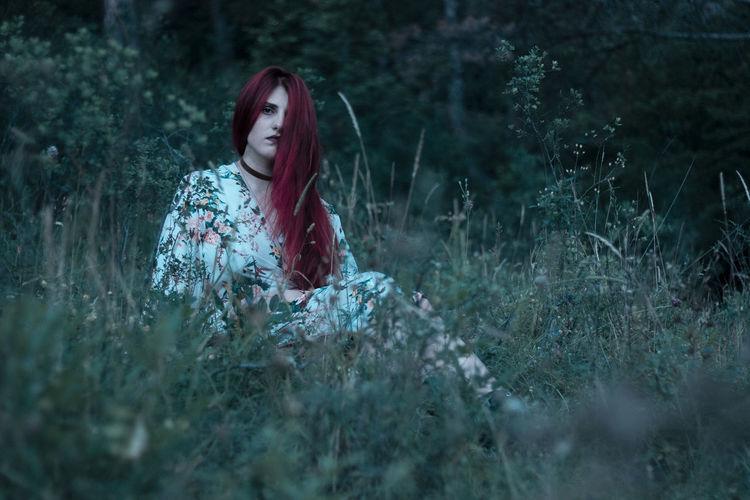 Portrait of woman sitting amidst plants