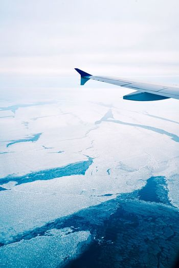 Close-up of airplane wing over sea during winter