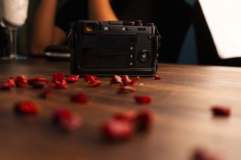 Camera - Photographic Equipment Close-up Human Body Part Indoors  Leisure Activity Lifestyles Men Midsection Music One Person Photography Themes Real People Red Selective Focus Surface Level Table Technology Wood - Material